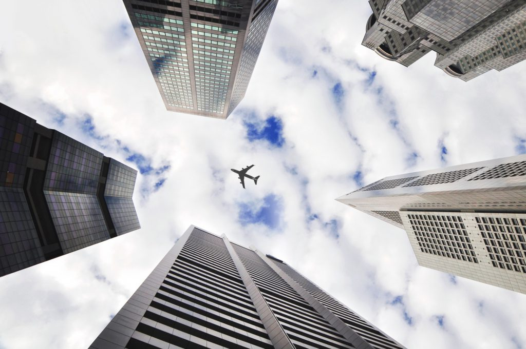 Airliner overhead surrounded by skyscrapers